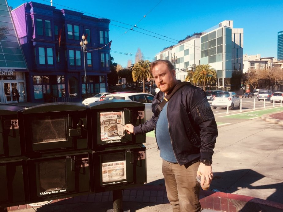 Drew pointing out the cover of the SF Examiner. He did a few stand-up comedy sets at Oakland's Feelmore adult sex shop and the place is struggling to stay afloat because of the high cost of living and sky-high rent. Support local businesses!
